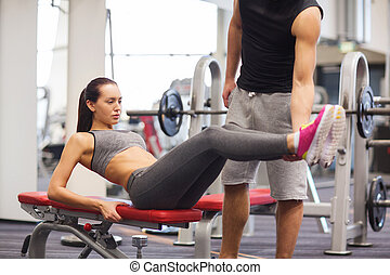 woman with trainer doing abdominal exercise in gym