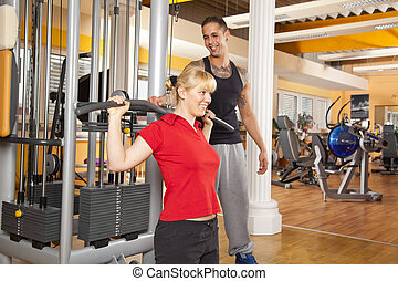 A smiling beautiful young woman in her twenties exercising in a fitness studio training her latissimus and being instructed by her personal trainer