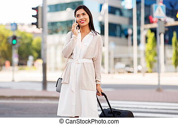 woman with travel bag calling on cellphone in city