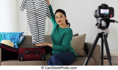 blogging, tourism, technology, mass media and people concept - happy smiling woman or blogger with camera recording video and packing clothes to travel bag at home for videoblog