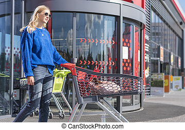 woman with trolley at the supermarket door