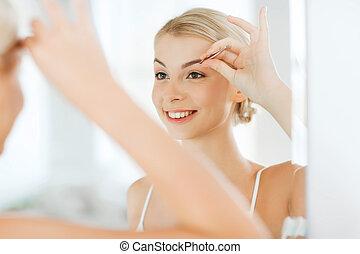 woman with tweezers tweezing eyebrow at bathroom - beauty ...