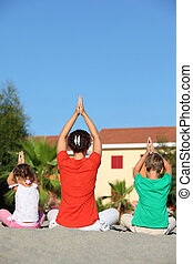 Woman with two children sit turn  back on sand in  pose of yoga and laying down hands lift hands upwards