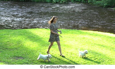 Woman with two dogs pets have a walk near river in park. Handheld shot.