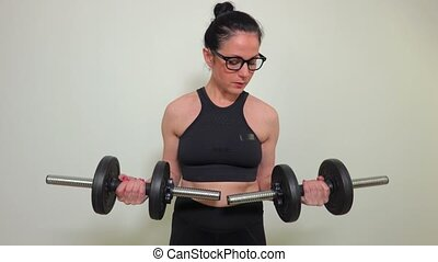Woman with two dumbbells doing exercises for biceps