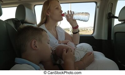 Woman with two kids traveling by car