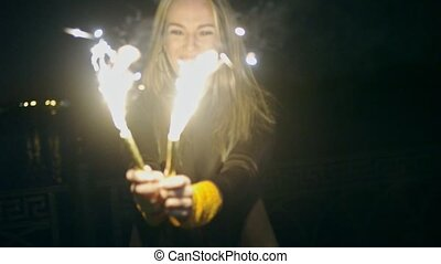 Woman with two sparkler. Blurred woman with burning sparkler on dark background with lights