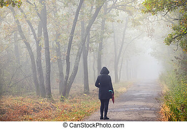 Woman with umbrella and foggy forest