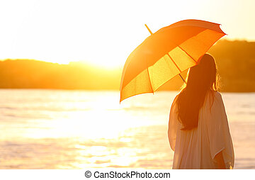 Woman with umbrella at sunset on the beach