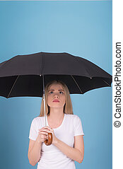 Woman with umbrella. Beautiful young blond hair woman holding umbrella and looking up while isolated on blue