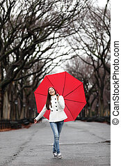 Woman with umbrella in fall in rain