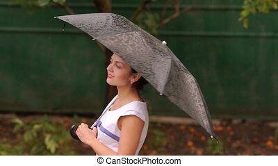 woman with umbrella in the rain - young beautiful woman with...