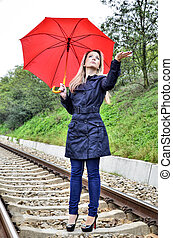 Woman with umbrella on railroad