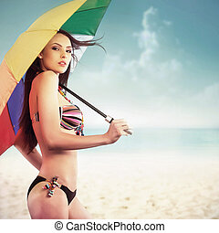 Woman with umbrella on the beach