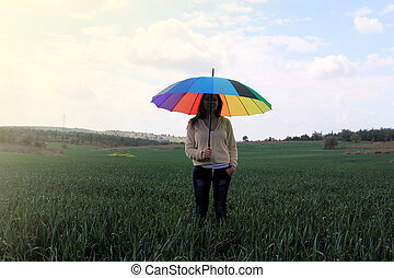 Woman with umbrella on the meadow