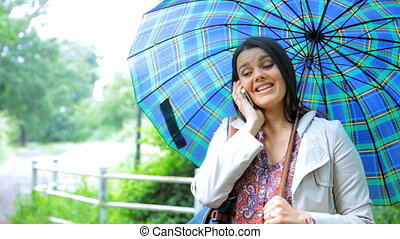 Woman with umbrella on the phone