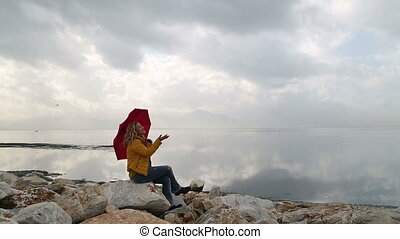 Lonely woman with umbrella, sitting on the rock at the seashore