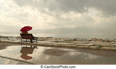 Woman with umbrella sitting on a be