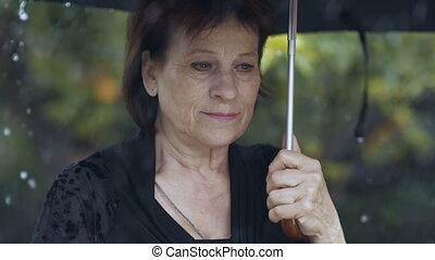 Woman with umbrella under rain - Sad woman under umbrella at...