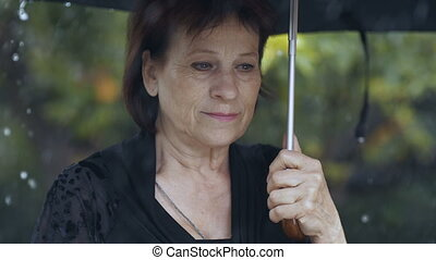 Woman with umbrella under rain - Sad woman under umbrella at...