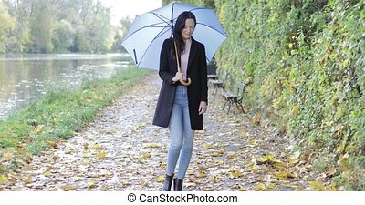 Woman with umbrella walking near pond - Attractive woman in...