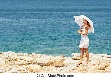 Woman with umbrella Walking on the Beach