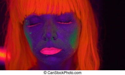 Woman with UV fluorescent makeup - Closeup woman face with...