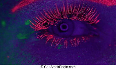 Woman with UV fluorescent makeup - Closeup woman's eye with...