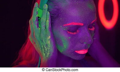 Woman face with fluorescent make up listening music with headphones, creative makeup great for nightclubs. Halloween party, shows and music concept - fast motion video