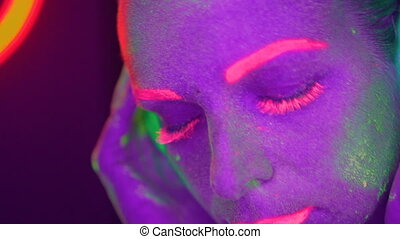 Woman face with fluorescent make up listening music with headphones, creative makeup great for nightclubs. Halloween party, shows and music concept - slow motion video