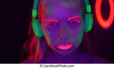 Woman with UV fluorescent makeup - Woman face with ...