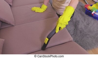 Woman with vacuum cleaner cleaning on sofa unavailable places