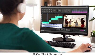 woman with video editor program on computer - technology, ...