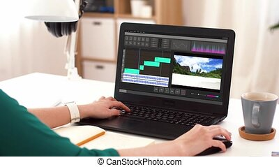 woman with video editor program on laptop at home -...