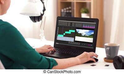 woman with video editor program on laptop at home - ...