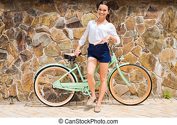 Woman with vintage bike. Full length of beautiful young smiling woman standing near her vintage bicycle