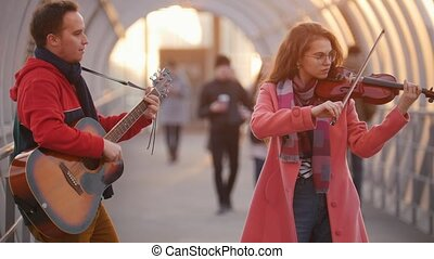 Woman with violin and man with guitar play in the overhead...