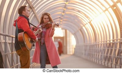Woman with violin and man with guitar play together on the...