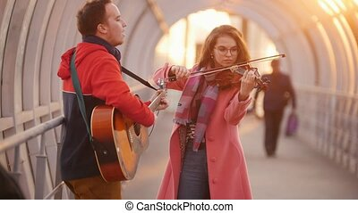 Woman with violin and man with guitar playing music on the...