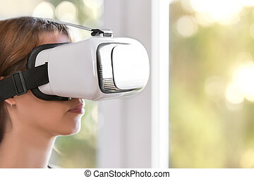 Woman with virtual reality glasses is standing in front of a window