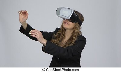 Woman with virtual reality glasses on her head on gray background at studio.