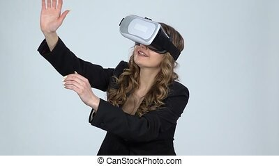 Woman with virtual reality glasses on her head on gray...