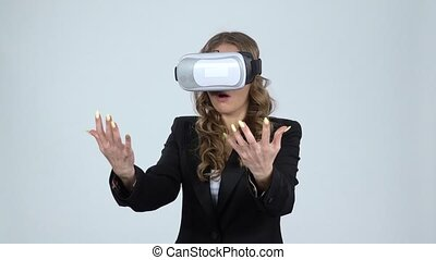 Woman with virtual reality glasses on her head on gray background, slow motion.