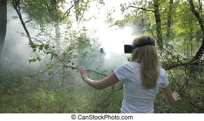 Woman with virtual reality headset goggles following vr ghost girl in smoke in the forest