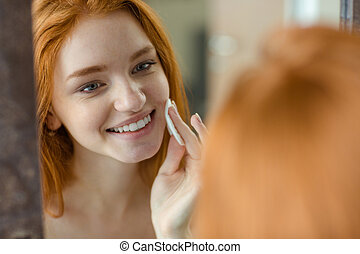 Woman with wadding looking at her reflection in mirror - ...