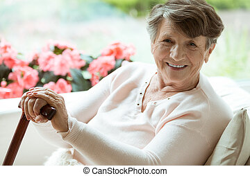 Woman with walking stick smiling - Elder lady sitting on the...
