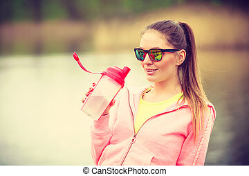 woman with water bottle after exercising workout