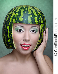 Woman with water-melon as helmet