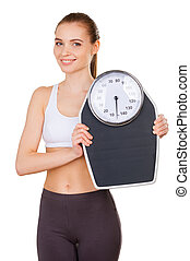 Woman with weight scale. Beautiful young woman in sports...
