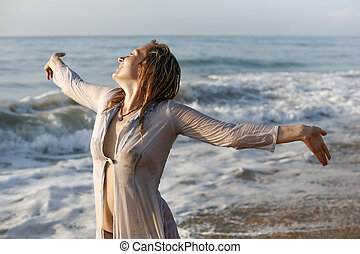 woman with wet hair - Woman in a wet dress at coast of the ...